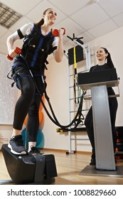 Caucasian woman training on stepper with weights in hands. Female trainer manages electric muscle stimulation purposed to increase effectiveness of training. Low angle view vertical shot