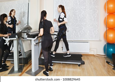 Caucasian woman training on treadmill in gym. Female trainer standing aside manages electric muscle stimulation purposed to increase effectiveness of training. Horizontal shot