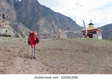 Caucasian woman trekker in Himalayan mountains near a stupa, Ladakh, India