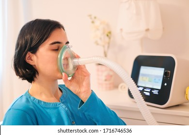 A caucasian woman using a cough assist ventilator mask for deep breaths, respiratory condition