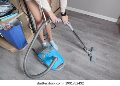 Caucasian woman with a vacuum cleaner in home.