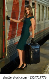 caucasian woman waiting at the railway station with a suitcase