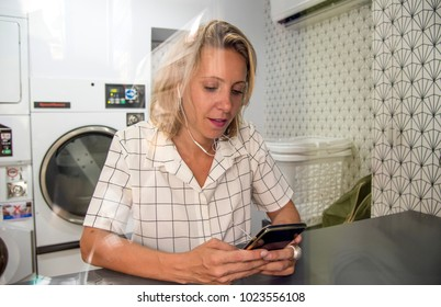 Caucasian woman waiting at the self service laundry
