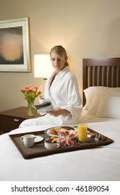 Caucasian woman wearing a bathrobe sits on a hotel bed with tray of breakfast. She is reading a newspaper and holding a coffee cup. Vertical format.