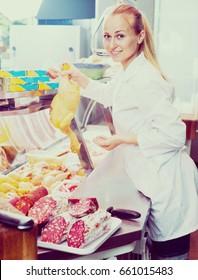 caucasian woman wearing coat selling fresh chicken carcass in delicatessen section