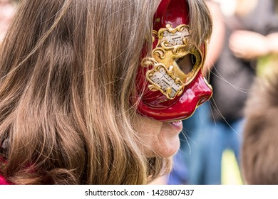 Caucasian Woman wearing colorful, decorative Venetian masquerade face mask to hide her identity.