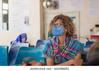 Caucasian woman wearing sanitary mask indoors while traveling in Vietnam. Tourist in waiting room with medical mask protection against risk of new corona virus covid-19 epidemy in Asia