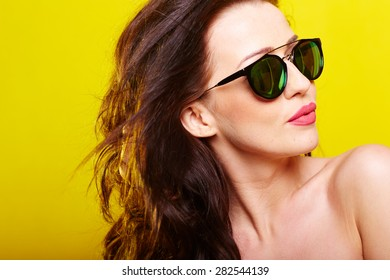 caucasian woman wearing sunglasses over yellow background