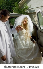 Caucasian woman in wedding gown getting off the car