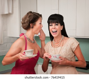 Caucasian woman whispers joke to friend in her kitchen