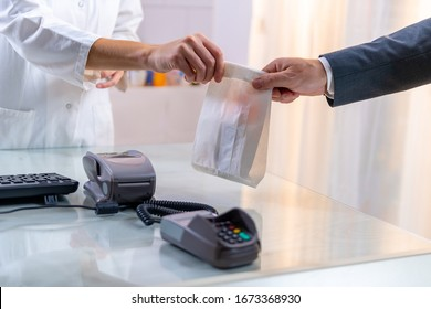 Caucasian woman in a white coat, standing behind the counter with keypad and POS terminal, gives a paper bag to a caucasian man