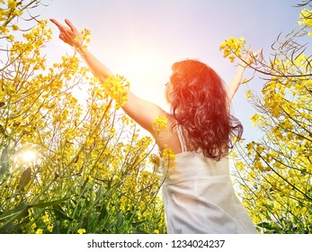 Caucasian woman in white dress standing back with raised hands in yellow flowers field. Summer vacation