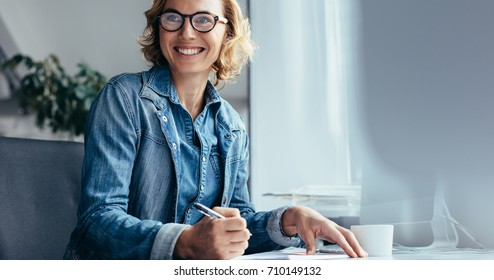 Caucasian woman working at her desk in office. Female executive looking away and smiling.