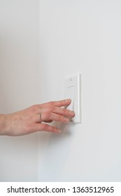 Caucasian womans hand flicking a light switch on and off