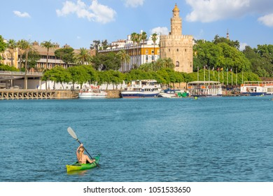 caucasian women in bikini canoeing at seville city and torre del oro at summer,Spain