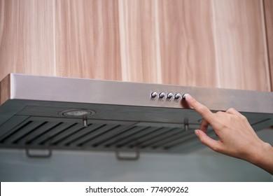 caucasian women hand using the range hood in modern kitchen
