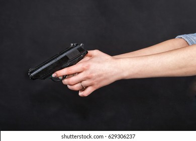 Caucasian women outstretched arms holding a black gun, fingers on the trigger. Against black background.