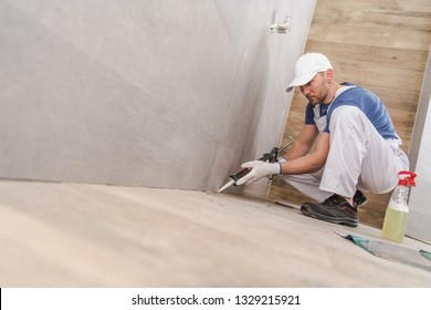 Caucasian Worker in His 30s Sealing Wall Corners of Ceramic Tiles Inside Newly Remodeled Bathroom. Using Silicone Sealant.