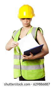 Caucasian young adult woman in her mid 20s wearing reflective yellow safety helmet and safety vest, looking down at a clipboard she's holding. Isolated on white background.