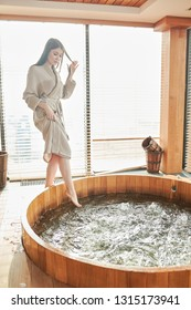Caucasian young brunette girl relaxing in jacuzzi in spa center, refreshing her body and mind