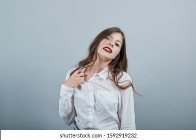 Caucasian young brunette woman over isolated gray background wearing casual white shirt, pulls back his shirt, looking serious. People lifestyle concepte.