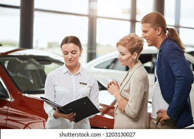 Caucasian young couple choosing luxury car in auto dealership looking at the interior, asking female seller about car features.
