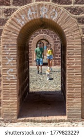 A caucasian young couple and their dog walking through an arched bridge in a sunny morning day