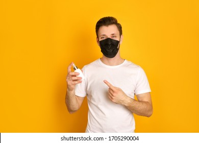 Caucasian young guy wears face black mask because of the pandemia of covid19 virus, stays calm and safe, has a white t-shirt on, showing the with his finger, smiling