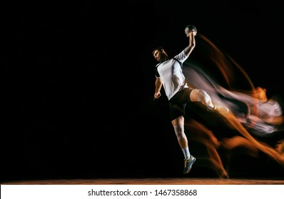 Caucasian young handball player in action and motion in mixed lights over black studio background. Fit male professional sportsman. Concept of sport, movement, energy, dynamic, healthy lifestyle.