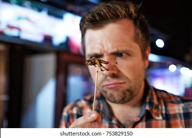 Caucasian young male eating cricket at night market in Thailand. Eating insect concept