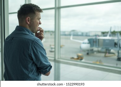 Caucasian young man is afraid to flight standing in terminal near window. Aerophobia concept