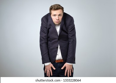 Caucasian young man in too big suit. He is offended and looking stressed. Looking silly in a suit of wrong size