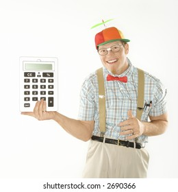 Caucasian young man dressed like nerd wearing beanie holding large calculator.