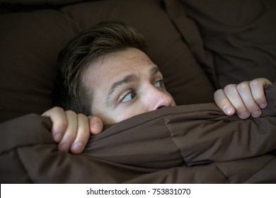 Caucasian young man hiding in bed under the blanket at home. He is stressed and tries run away from problems