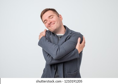 Caucasian young man hugging himself. Selfish european male.