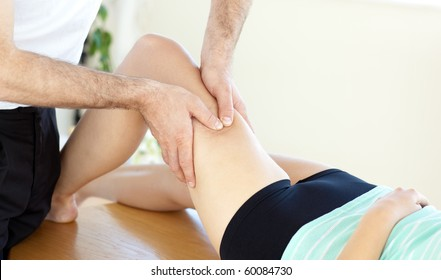 Caucasian young physical therapist giving a leg massage in a health center