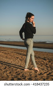 Caucasian young woman in black sweat shirt, blue jeans walking alone on the beach in the sunset. Outdoor portrait pensive or thoughtful girl with hairstyle posing on river sea background.
