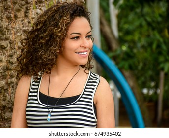 Caucasian young woman of curly hair smiling color by white