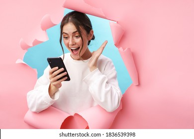 Caucasian young woman expressing surprise while holding cellphone isolated through pink background