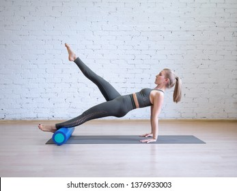 Caucasian young woman in grey sports suit doing pilates workout on math with roller, loft style background, toned light blue. Wellness, recovery, rehabilitation, prevention spine desease, smart body