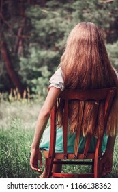 Caucasian young woman with long blond hair resting on nature on wooden chair, back view, close-up, outdoor air, toned