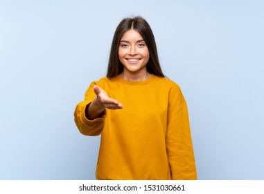 Caucasian young woman over isolated blue wall handshaking after good deal