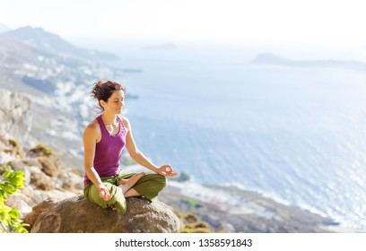 Caucasian young woman practicing yoga while sitting in lotus pose on cliff over sea