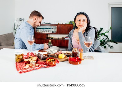 caucasian-hispainic couple at dinner. Unsatisfied woman annoyed while her mobile phone addict husband is texting and ignoring her