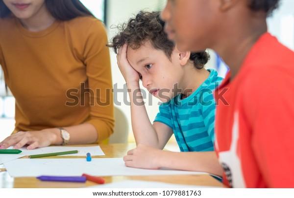 Caucasion boy kid with sadness emotion sitting in classroom in kindergarten preschool.bulying depression concept
