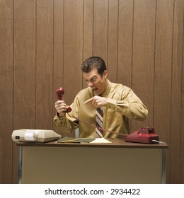 Caucasion mid-adult retro businessman sitting at desk pointing at telephone in anger.
