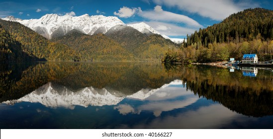 Caucasus. Abkhazia. Riza lake,  autumn yellow-green forest and white snow peaks, reflecting in the calm water of the lake. Panorama