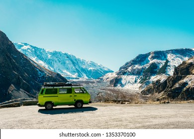 Caucasus mountain range/Georgia - 03/10/2019 - Vintage classic van parked beside the road among the high Caucasus peaks on the far north of Georgia. Breath taking view.