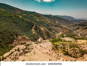 Caucasus Mountains from aerial view. Road trough mountain pass. Dramatic landscape and beautiful sky. Garni, Armenia.