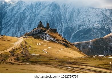 Caucasus mountains, ancient Gergeti Trinity church Tsminda Sameba against the glacier near mount Kazbek, landmark of Georgia